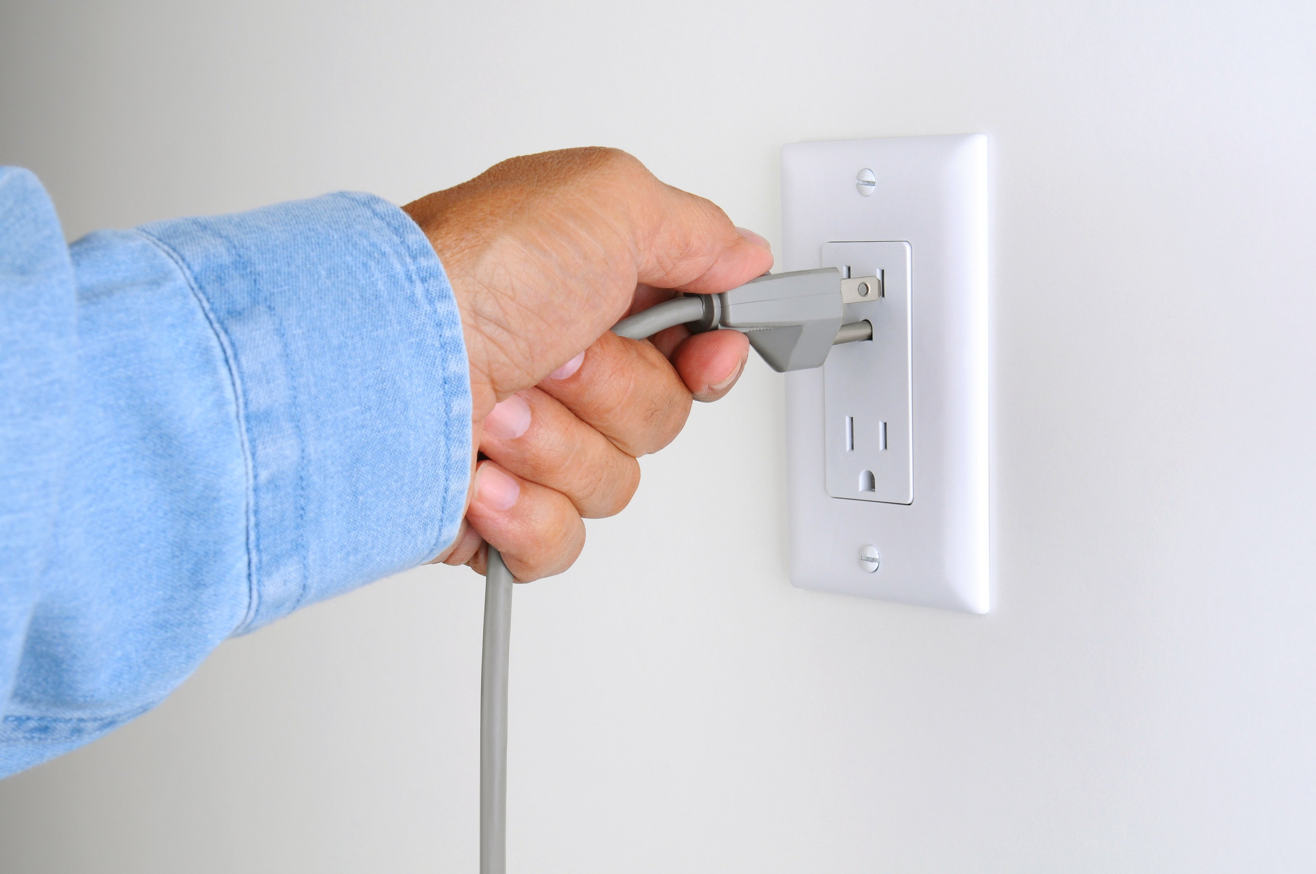 Electrician plugging appliance into socket